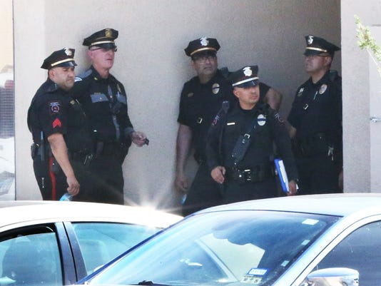 Law enforcement officers congregate outside the entrance to a building at 880 Anthony Drive following a shooting incident Tuesday in Anthony, N.M.