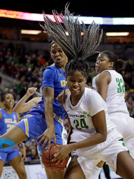 Oregon's Ruthy Hebard (24) comes down with a rebound in front of UCLA's Lajahna Drummer as Oregon's Oti Gildon, right, watches during the second half of an NCAA college basketball game in the semifinals of the Pac-12 women's tournament Saturday, March 3, 2018, in Seattle. Oregon won 65-62. (AP Photo/Elaine Thompson)