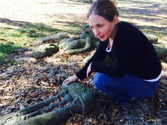 Allysa Browne Peyton, assistant curator of Asian art at the Samuel P. Harn Museum of Art at the University of Florida, examines a stone carving on the grounds of the Museum of the Apopkans in Apopka, Florida. The stone sculptures were about to be disposed of until Peyton determined they were from the East Java area of Indonesia and possibly 1,000 years old.
