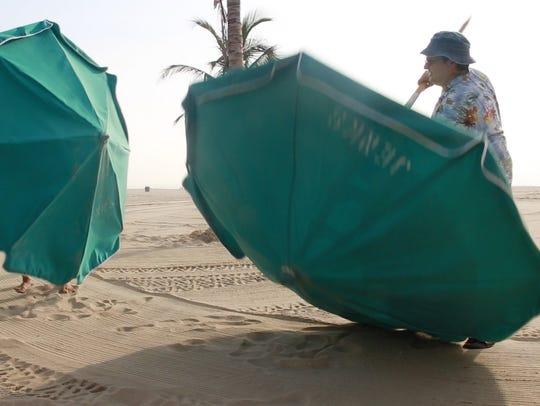 Jeerry Carino helps set up the beach umbrella stand