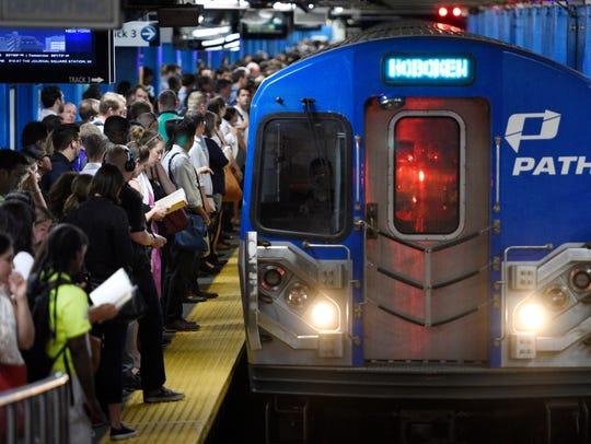 Commuters wait to board an incoming Hoboken PATH train