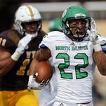 North Dakota running back John Santiago runs away from Wyoming defender Eric Nzeocha during the first quarter of the Bison's 24-13 win Saturday over the Cowboys in Laramie.
