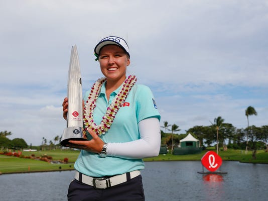 Brooke Henderson, of Canada, holds the trophy after winning the LPGA Lotte Championship golf tournament Saturday, April 14, 2018, in Kapolei, Hawaii. (Jamm Aquino/The Star-Advertiser via AP)/The Star-Advertiser via AP)