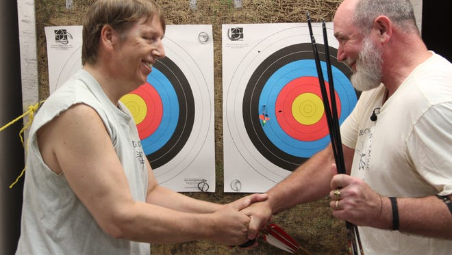 Archery instructor Lyle Maryniak of Wauwatosa, right, congratulates Tony Jandrowski of Milwaukee after Jandrowski, who is blind, shot a tight three-arrow group during a program at West Town Archery in Brookfield, Wis.
