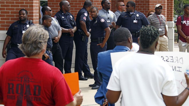 """Campus police watch a small group of protestors at the Raymond campus of Hinds Community College Wednesday protest the arrest of a student for """"failure to comply"""" for not showing his student identification. The protestors believe the arrest last week came after the student was initially targeted for a dress code violation of wearing sagging pants."""
