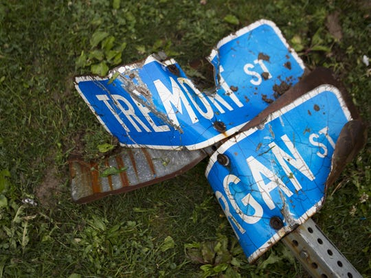 The street sign to Tremont and Morgan Streets lies twisted on the ground on Sunday, May 31, 2015.