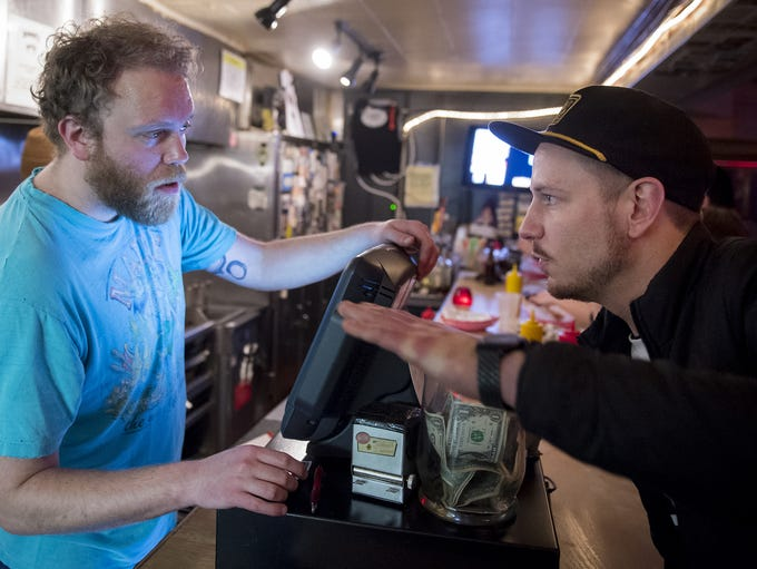 Bartender Jeremy McAnulty, left, takes an order from