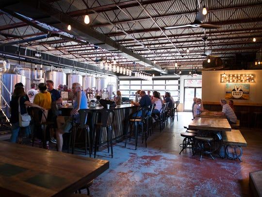 Customers enjoy beer at Swamp Rabbit Brewery in Travelers