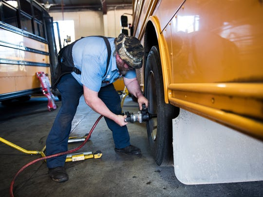 Clifton Walker removes school bus wheels for replacement at a Greenville County Schools bus maintenance facility on Thursday, Nov. 16, 2017.