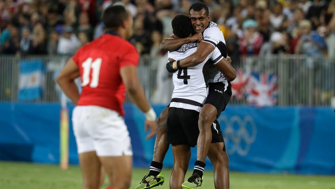 Fiji's Apisai Domolailai, facing camera, is hugged by Viliame Mata after winning the gold medal match against Britain in the mens rugby sevens at the 2016 Summer Olympics in Rio de Janeiro, Brazil, Thursday, Aug. 11, 2016.