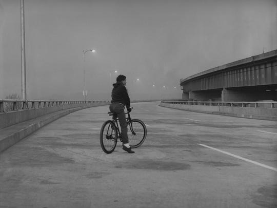 Probably the first user of the Louisville-New Albany bridge on oepning day today was Bobby Manning, 13, of South Western Parkway, in Louisville. Manning is shown before dawn on the Louisville approach with Indiana in the background. By Bud Kamenish, The Courier-Journal. Dec. 22, 1961