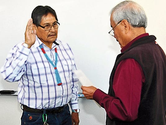 At left, Johnson Dennison, a new member of the Diné College Board of Regents, is sworn into office by Laurence Gishey, the board's president, during a board meeting Friday in Tsaile, Ariz.