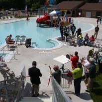 Wausau mayor Jim Tipple, lower left, cuts the ribbon Wednesday at the grand reopening of Kaiser Pool in Wausau.