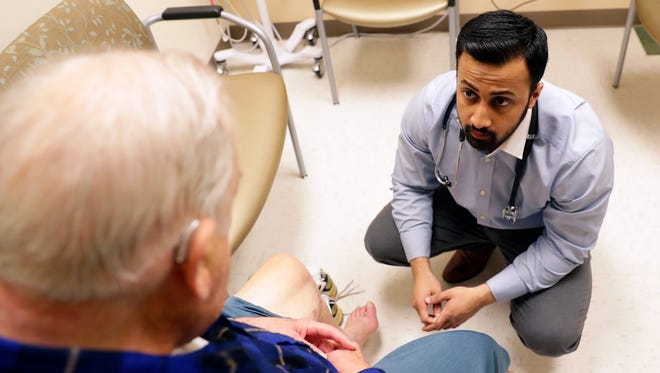 Dr. Waqas Yasin, examines a patient Feb. 22, 2018 at the Milo C. Huempfner VA Health Care Center in Green Bay, Wis. Yasin, originally from Pakistan, is one of four residents participating in the new Northeastern Wisconsin Psychiatry Program, which includes general medical and mental health training. Sarah Kloepping/USA TODAY NETWORK-Wisconsin