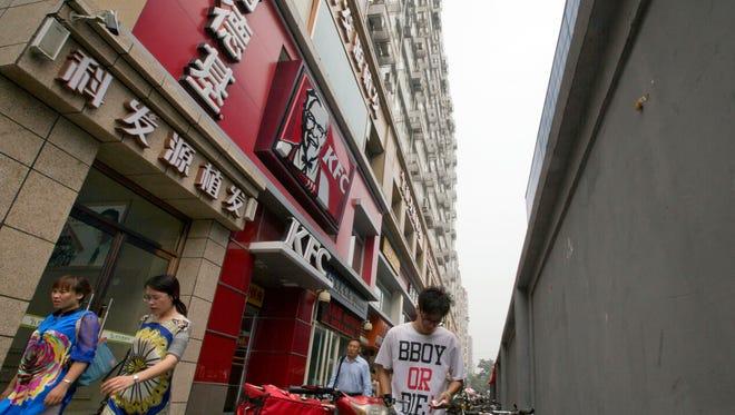 Pedestrians pass by a KFC restaurant in Beijing, China, Thursday, July 31, 2014.