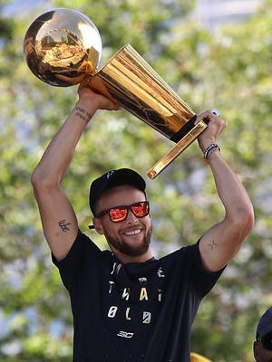 Golden State Warriors star Stephen Curry holds the Larry O'Brien NBA Championship Trophy during the Warriors Victory Parade on June 15, 2017.