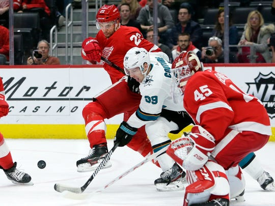 Detroit Red Wings defenseman Patrik Nemeth (22), of Sweden, and San Jose Sharks center Logan Couture (39) battle for the puck in front of Red Wings goaltender Jonathan Bernier (45) during the first period of an NHL hockey game Tuesday, Dec. 31, 2019, in Detroit. (AP Photo/Duane Burleson)