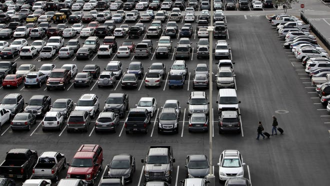 Pedestrians walk through the sea of cars at Phoenix Sky Harbor's East Economy parking lot as seen in Phoenix on Dec. 15, 2014.