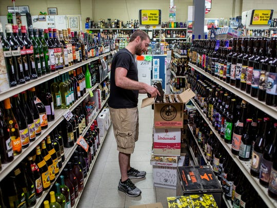 Nate Bakko works on pricing and stocking beer Wednesday,