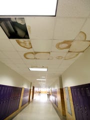 Water leaks drip through the ceiling and into the hallway,