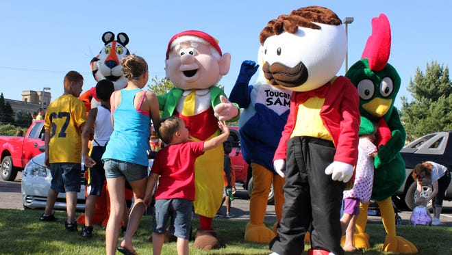 In this 2012 photo, children rush to get hugs from the characters representing Kellogg's, Post and Ralston before the Cereal Festival Parade kicked off in downtown Battle Creek.