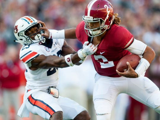 Alabama quarterback Jalen Hurts (2) stiff arms Auburn defensive back Johnathan Ford (23) during the Iron Bowl at Bryant Denny Stadium in Tuscaloosa, Ala. on Saturday November 26, 2016.