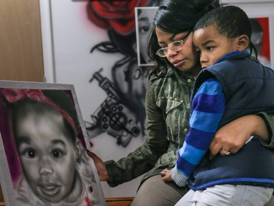 Zinnia Davila and her 3-year-old son Aston Davila-Torres look at a portrait of Davis' 16-month-old daughter, A'Niah Davila-Torres, who died August 2014. Daycare worker Latoya Tomlin was indicted last week for the murder of A'Niah.