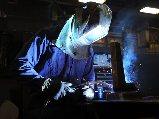 Ryan Triatik welds a piece of metal at Manowske Welding. Triatik, who has been employed with the company about three years, began learning skills at Manowske as part of a school-to-work program while a student at Horace Mann High School. A 2012 high school graduate, he has continued his education at Moraine Park Technical College.