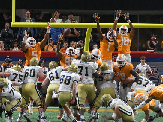 The Tennessee line leaps to block an extra point by