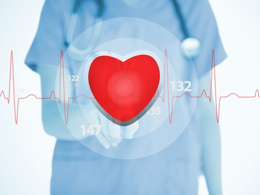 Nurse in scrubs touching red ECG line with heart graphic
