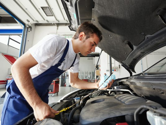 Young mechanic checking the oil level of a car