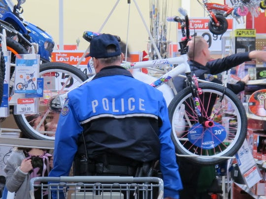 An officer stands to the side while a Walmart associate gets a bike down from the rack for a Shop with a Cop participant in 2012.