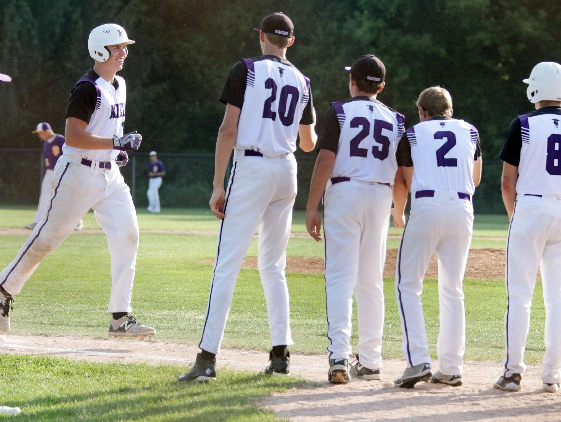 Kiel's Austin Goehring (11) is greeted by teammates after hitting a two-run home run in the fourth inning against Sheboygan Falls on Friday.