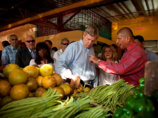 Then-Agriculture Secretary Tom Vilsack speaks with Provincial Agriculture Deputy Julio Martinez during a visit to a local farmers market in Havana, Cuba, Nov. 13, 2015.