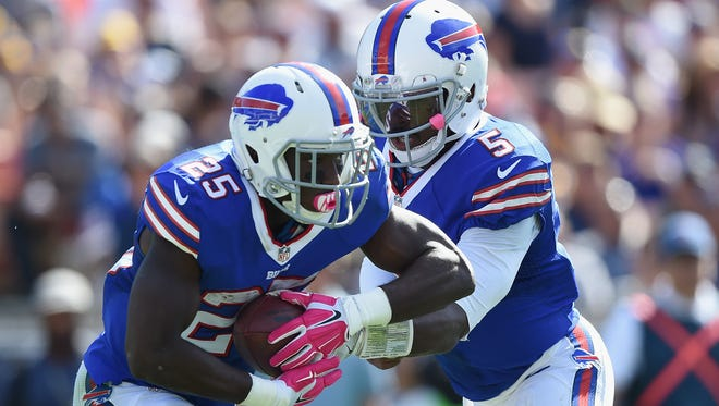 Quarterback Tyrod Taylor of the Buffalo Bills hands off to teammate LeSean McCoy during the second quarter of the game against the Los Angeles Rams at the Los Angeles Memorial Coliseum on October 9, 2016 in Los Angeles, California.