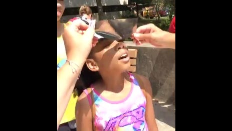 A young eclipse viewer at Rowan University looks at the sun through foil material that's used inside eclipse glasses.