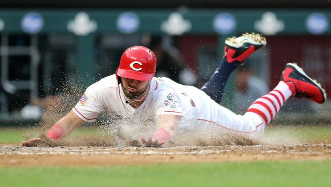 Cincinnati Reds right fielder Jesse Winker (33) slides in to score in the fourth inning during an interleague baseball game between the Chicago White Sox and the Cincinnati Reds, Wednesday, July 4, 2018, at Great American Ball Park in Cincinnati.