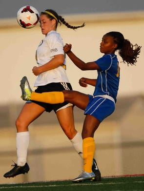 Padua's Regan Lehman (left) and Caesar Rodney's Janiah Moore rush for the ball.  Padua takes on Caesar Rodney for the Division I DIAA Girls State Championship Monday June 2, 2014 at Smyrna High School.