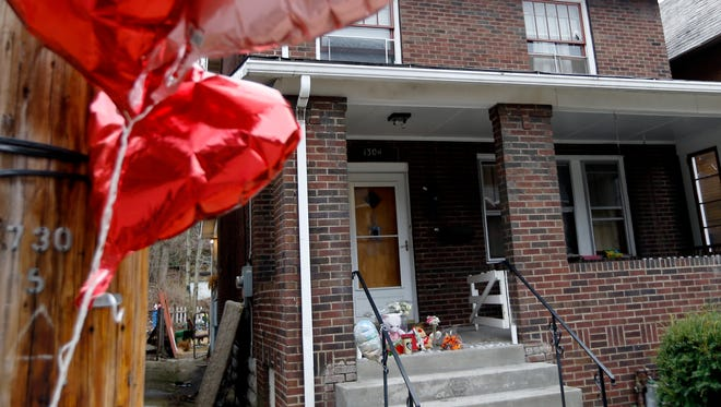 Balloons hang from a pole near a makeshift memorial on the front porch of a house Friday in Wilkinsburg, Pa. A shooting at a backyard party of the house killed and wounded multiple people on Wednesday night in the suburb east of Pittsburgh.