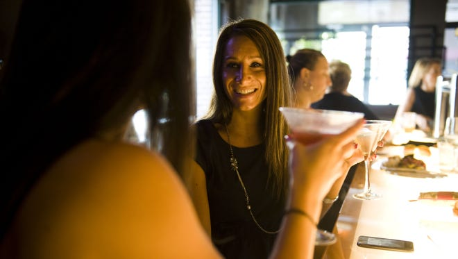 Ashley Radcliffe (left) of Pennsauken and Nicole Gaspari of Cherry Hill enjoy a drink at the bar in Catelli Duo restaurant in Voorhees. The eatery is reaaching out to wounded service members.