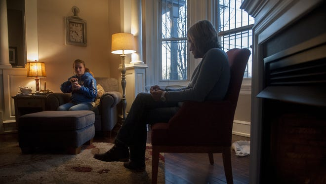 Brenda Antinore, right, sits in her South Camden home and talks with a woman named Dana who is taking the first steps toward recovery from drug addiction.