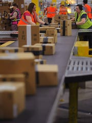 An Amazon warehouse workers prepare packages for consumer