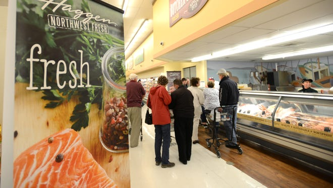 Customers browse the offerings at Haggen grocery store during the opening on Tuesday, April 28, 2015, in Keizer.