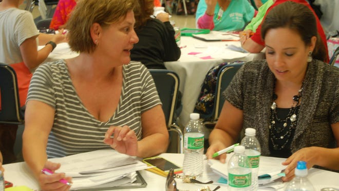 Sixth-grade literacy teacher Jill Ryan (left) and seventh-grade math teacher Sharlene Kreager participate in an activity during a response to intervention training Thursday at Hackler Intermediate School. Teachers learned strategies to help students perform at grade-level expectations or higher.