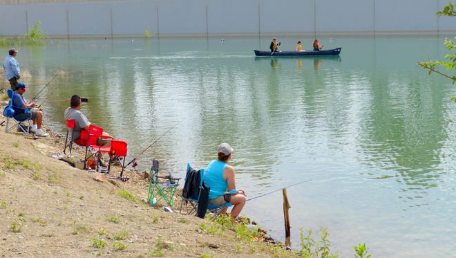 One family tries canoeing while other fished during the annual Youth Fishing Day at Grindstone Lake in Ruidoso.