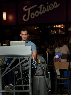John Jenkins of Orlando enjoys Tootsies Orchid Lounge as the travels through the Nashville International Airport Wednesday, June 20, 2018, in Nashville, Tenn. The airport authority has plans to change their vendor contracts which may effect current restaurants available to travelers.