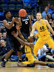 Xavier guard Quentin Goodin, left, battles for the ball with Marquette guard Duane Wilson, center, during the first half.