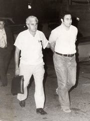 "New York Police Detective John Falotico escorts David Berkowitz Aug. 11, 1977 outside his Yonkers home at 35 Pine St. Berkowitz was arrested as the ""Son of Sam."" (The Journal News/file photo)"