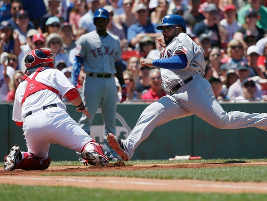 Boston Red Sox's Sandy Leon, left, positions at the plate as Texas Rangers' Prince Fielder, right, scores on a two-run single by Rougned Odor during the first inning of a baseball game in Boston, Monday, July 4, 2016. (AP Photo/Michael Dwyer)
