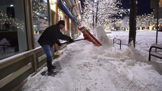 Tom Gorman shovels snow outside his business, Dean's barbershop on Thursday, Jan. 5.